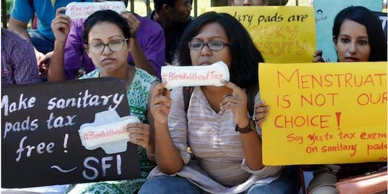 three women with signs make sanitary pads tax free
