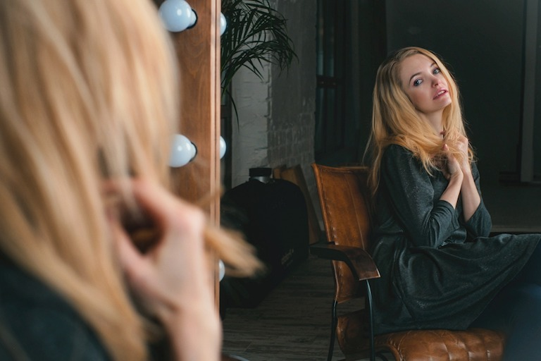 woman sitting in brown leather chair looking at herself in mirror